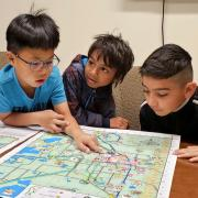 Whittier Elementary first-graders Sean Lee, from left; Tevin Loku Umagiliyage and Eber Garcia-Gonzalez get their first look at a kid-friendly map of Boulder they helped create through Growing Up Boulder. Growing Up Boulder, a collaboration among Boulder, the Boulder Valley School District and the University of Colorado Boulder, worked with about 700 elementary students for the project.