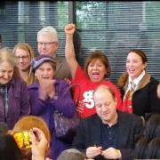 Governor Polis signs a bill surrounded by mobile home activists celebrating