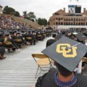 A graduation ceremony from the back with CU on a student's cap in the foreground.
