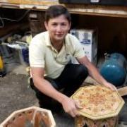 Marufjon (Maruf) Mirakhmatov squats next to a small table from the Boulder Dushanbe Teahouse.