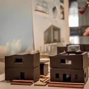 Person points to a model of a house.