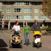 Parents walking with kids in strollers in Vancouver Park