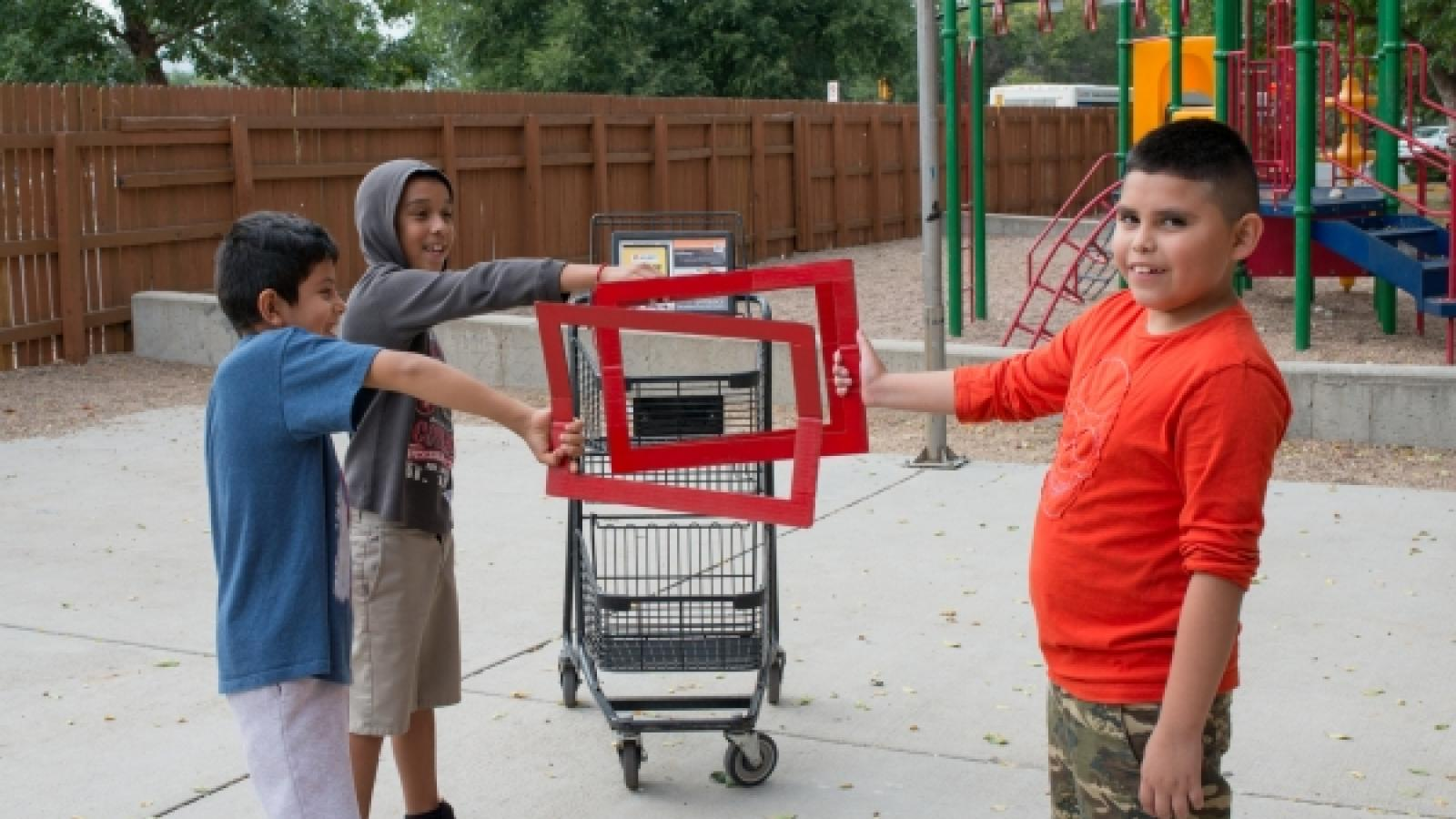 Three children hold red frames around an abandoned cart in a playground, signifying they don't like to see carts in their playgrounds.