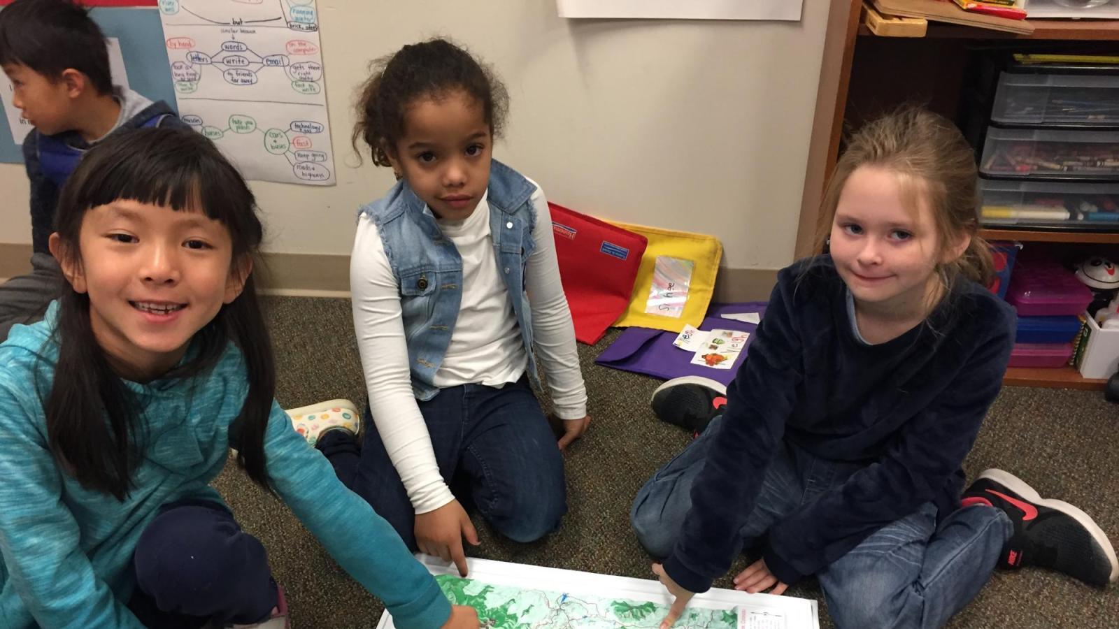 Three children sitting around a map.