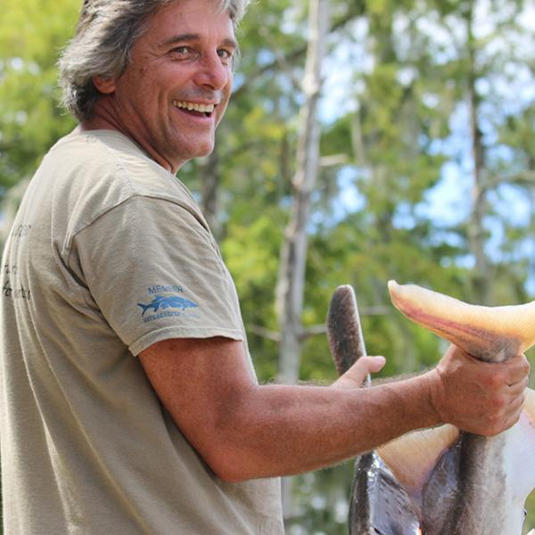 Tour guide smiling, getting ready to release large paddlefish