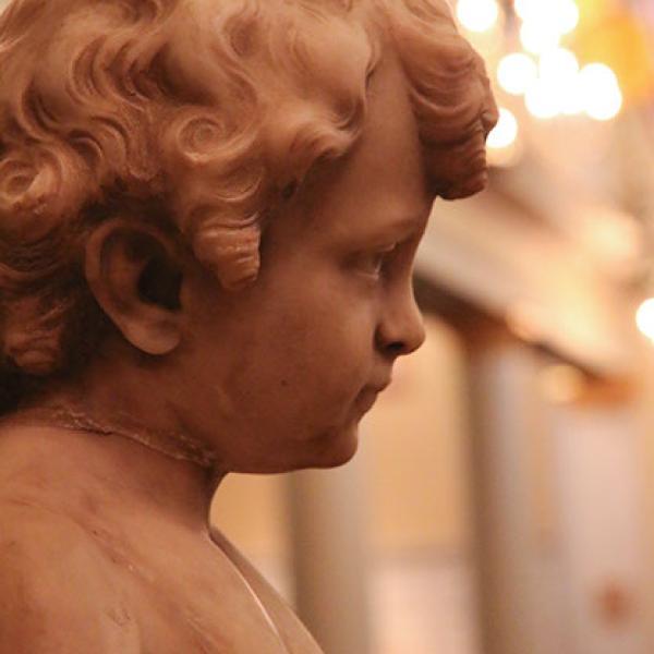 A statue of a cherub's head in profile