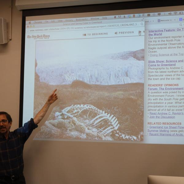 Michael Kodas points to projection display of an image of a glacier