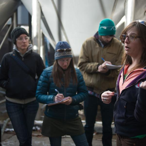 Science writing students taking notes on a field trip to a brewery