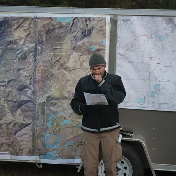 Heil Ranch map displayed on the fire fighters equipment trailer and a fire fighter looking at a map