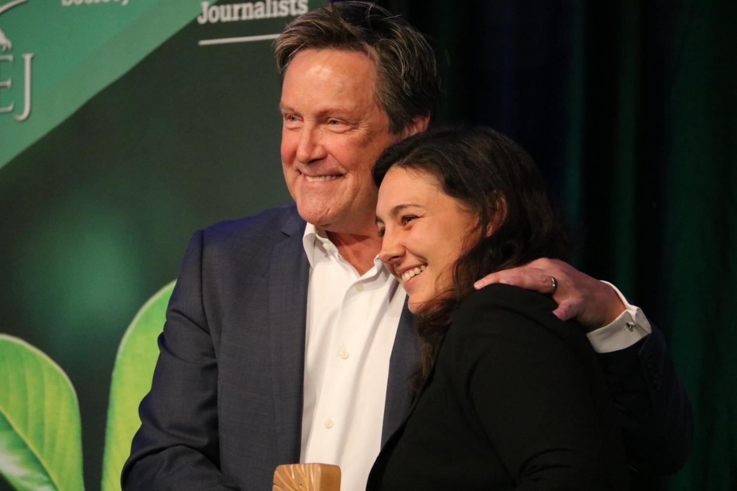 Jeff Burnside embraces Lindsey Fendt as she accepts the award for Outstanding Investigative Reporting, Small Market. Photo by Kelsey Simpkins