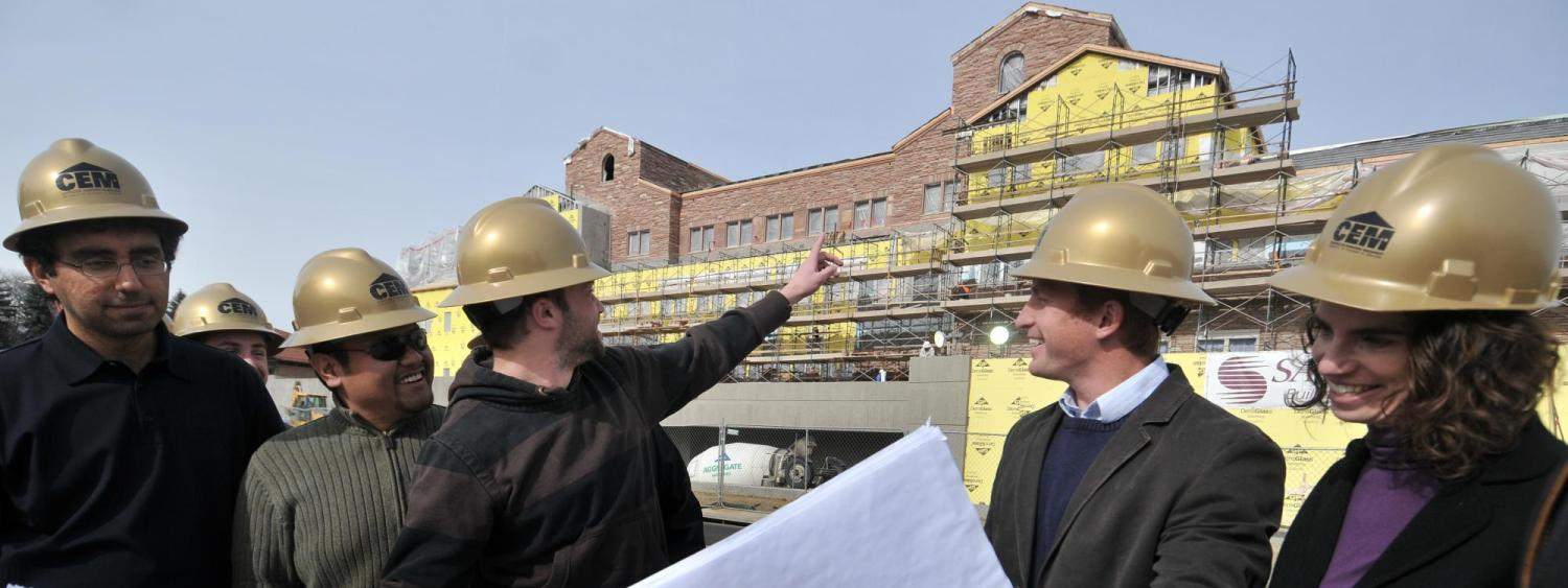 CEM faculty and students look over blueprints at a construction site.