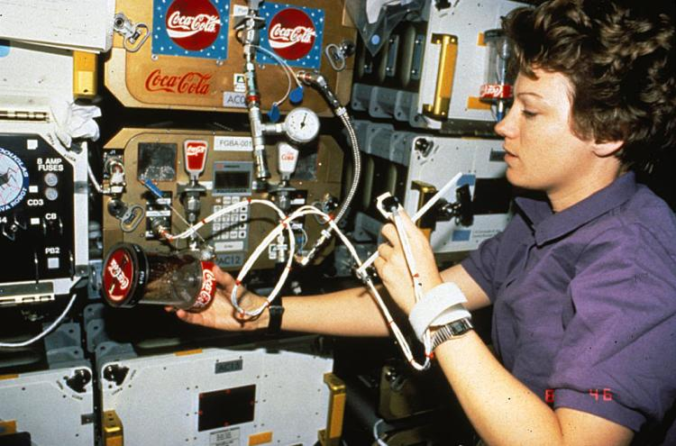NASA astronaut Eileen Collins measuring her heart rate with FGBA-2 while holding an FTU filled with Coke