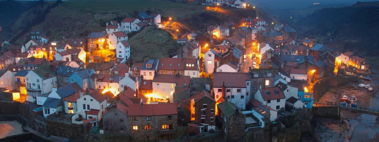 Houses all lit up in a small English village at night.