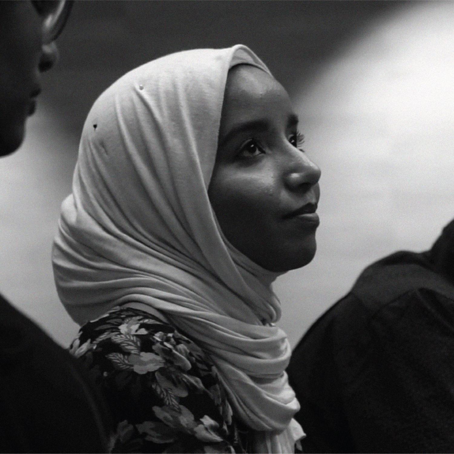 A Sudanese woman looks up into the distance.