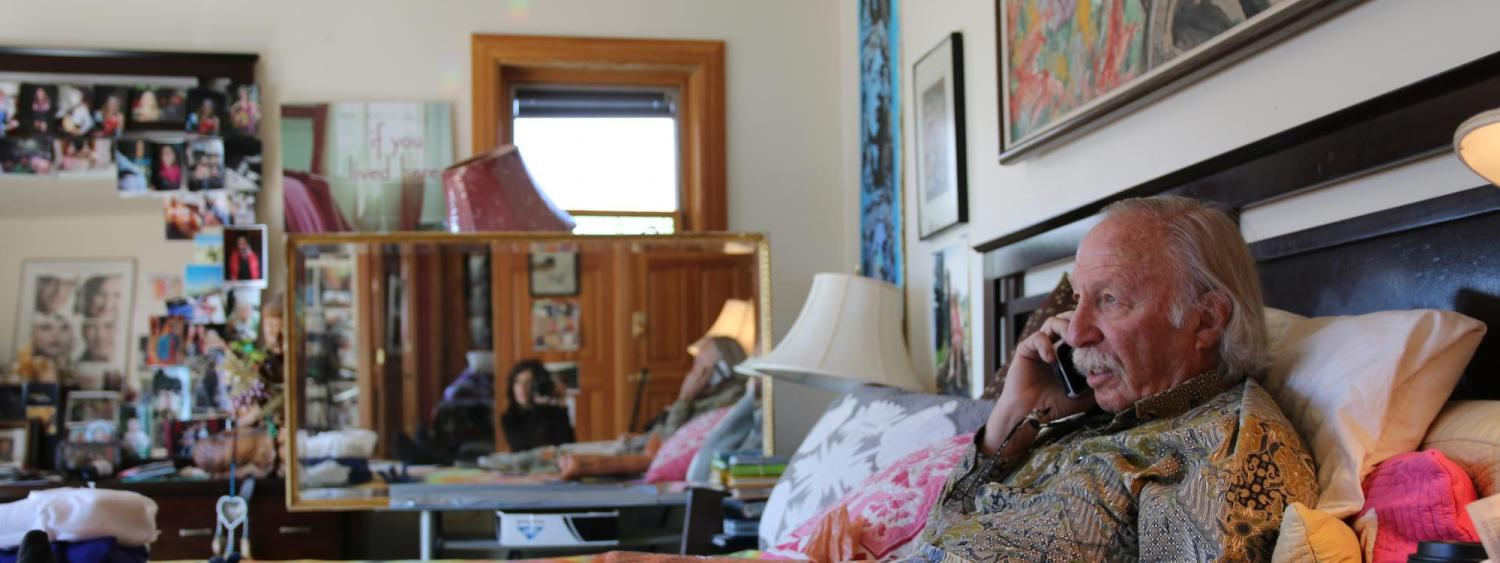 Man on bed with filmmaker Lynne Sachs visible in a mirror in the background. Still from Sachs's doucmentary Film About a Father Who (2020).