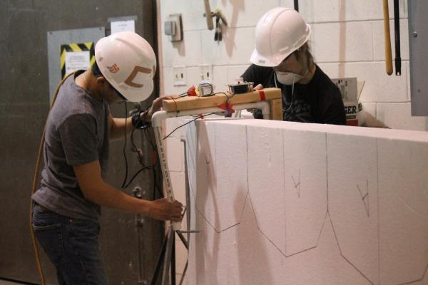 Two members of the concrete canoe team cut Styrofoam for their concrete mold.