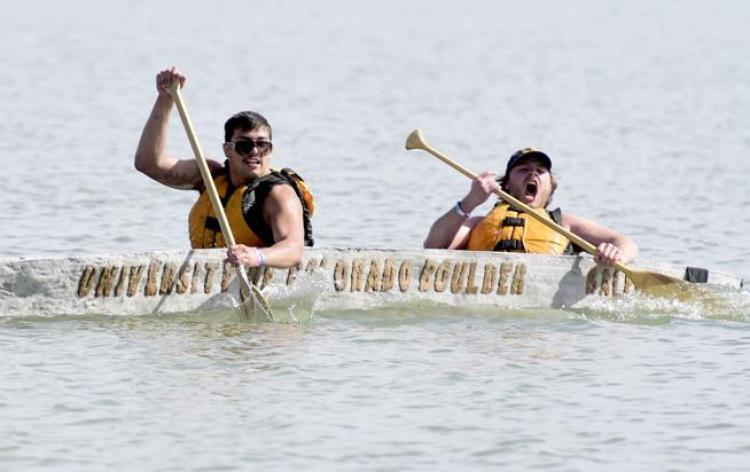 Two students paddle towards the finish in their concrete canoe