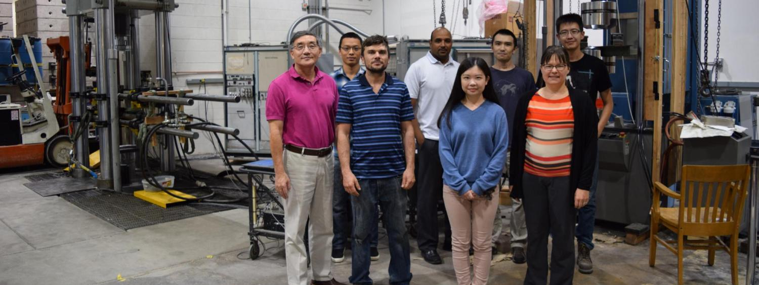 A group shot of Yunping Xi, Mija Hubler and their students in the structures lab.