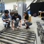 A group of students discuss the design of their steel bridge
