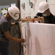 Two students cut Styrofoam to make the mold for the concrete canoe