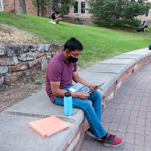 masked student sitting outside