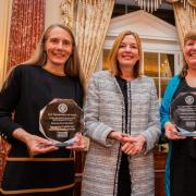 three women standing while two hold awards