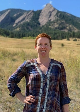 Laura MacDonald standing in field with Flatiron Mountain backdrop