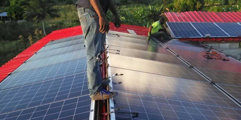 Man standing on solar panels in Haiti