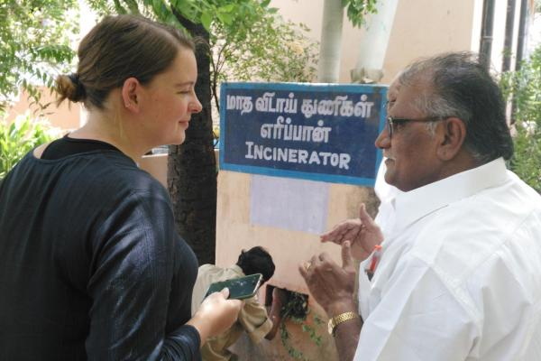 Student Allie Davis speaks to a man, next to a bilingual sign