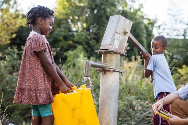 Kids pumping water at a hand pump