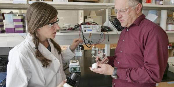 Professor Karl Linden shows a woman in a lab some equipment
