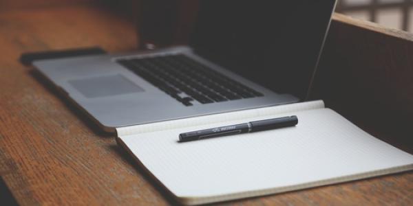 notebook sitting next to Mac