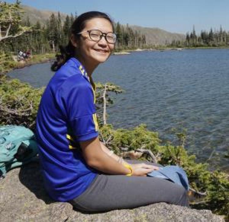 Naomi sits next to lake