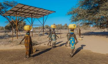 Women gathering water outside in Kenya with yellow buckets on their heads