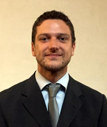 Photo of Carlo wearing dark suit, light shirt, and grey tie
