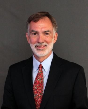 Man with grey beard smiling