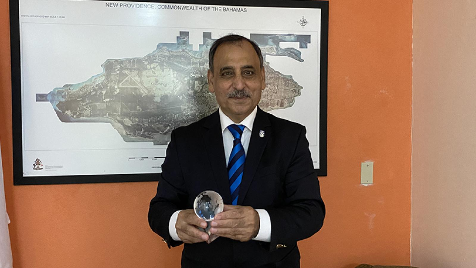 Dr. Sarim Al-Zubaidy holding his award in front of a map of the Bahamas