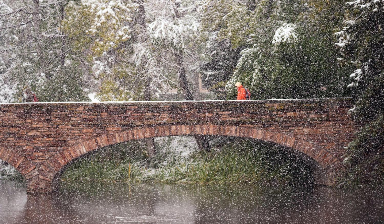 Snow falls as pedestrian crosses Varsity Bridge