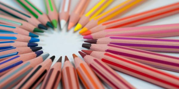 Colored pencils rest in a circle on a white surface