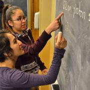 Two students work a chemistry problem at a blackboard