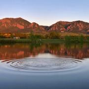 Boulder's Flatirons are shown at sunrise reflected across a pond