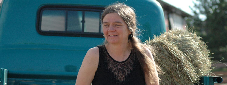 Patty Limerick smiling next to haystack