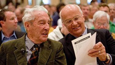 Secretaries Stewart Udall and James Watt looking at a program