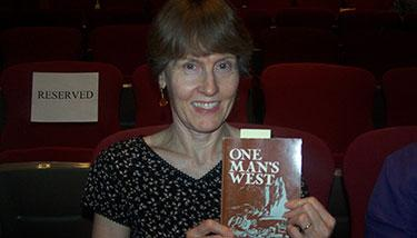 Sue Dean holding the book One Man's West
