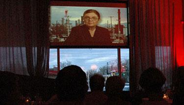 Audience watching Patty Limerick on projector screen