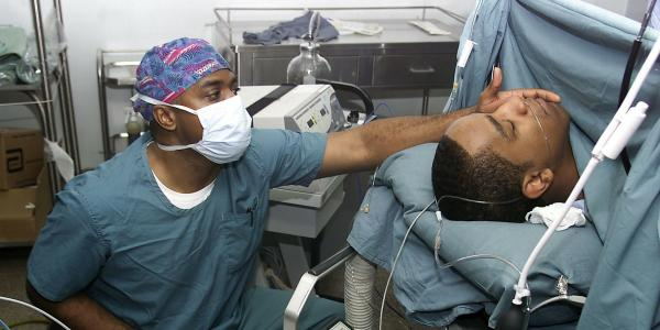 Anesthesiologist monitors patient.