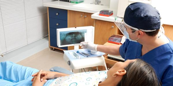 Dentist shows patient an x-ray.