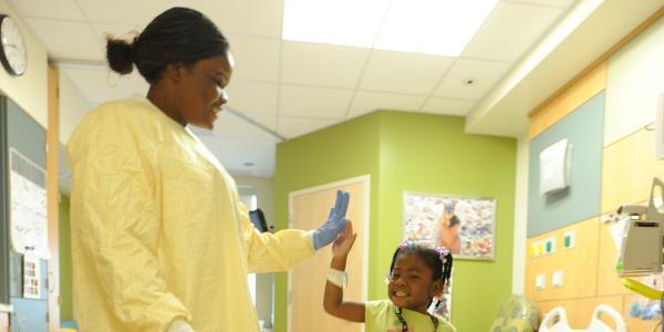 Nurse dances with young patient.