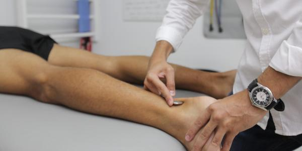 Physical Therapist works on patient's leg.