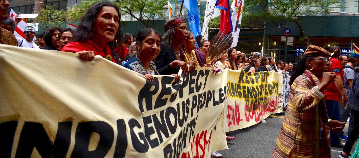 "A group marches in the Peoples Climate March holding a banner ""Respect Indigenous Peoples' Rights"""